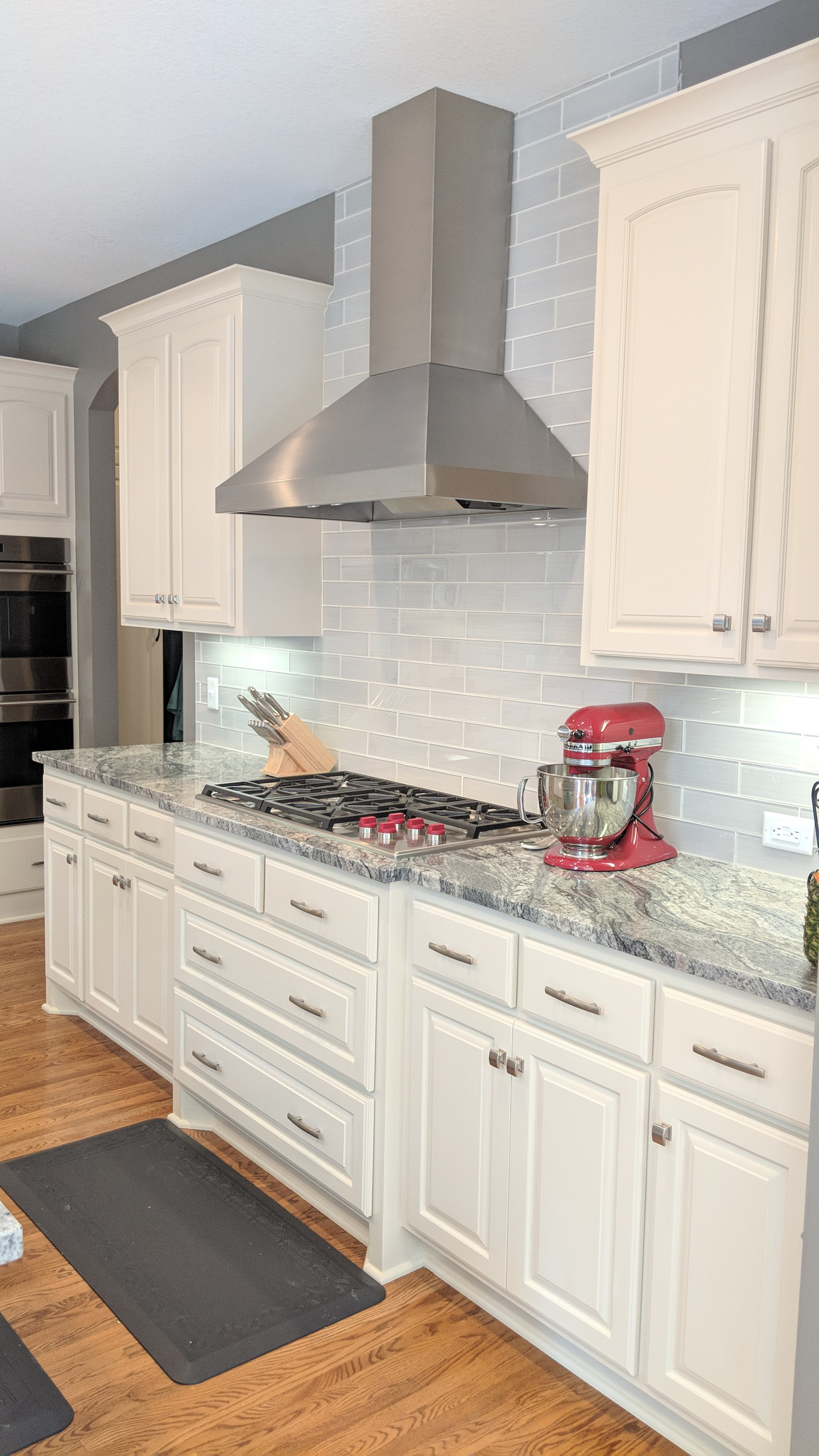 After - kitchen range wall new Granite tops  W/ glass subway tile