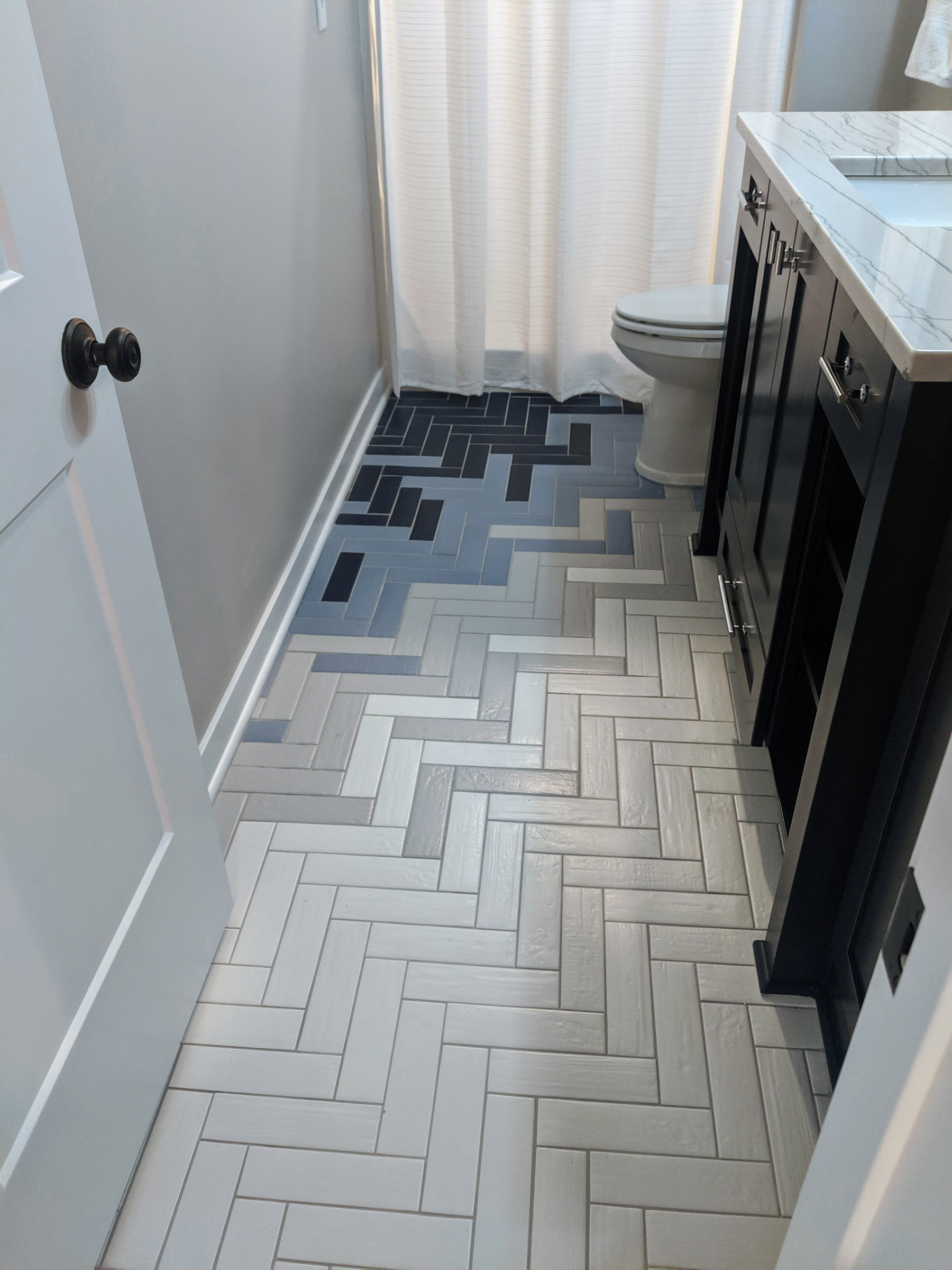 Herringbone tile pattern @ the ¾ bath with bleeding transfer of 4-colored tiles, brings a unique style to an otherwise boring bathroom tile