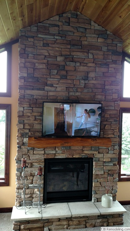 6' x 14' Stone fireplace w/ reclaimed timber mantle.