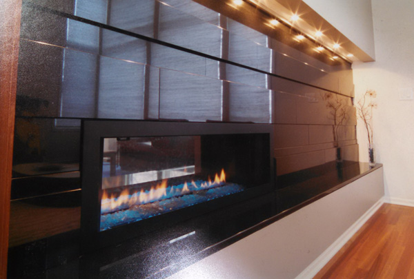 The fireplace wall (also viewable from the kitchen) is faced with gunmetal iridescent handmade tile made by Heath Ceramics, a women-owned firm that specializes in mid-century modern glazes